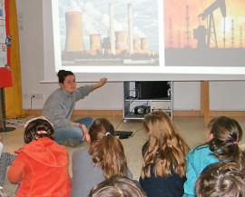Une animatrice présente à un groupe d'enfants les énergies fossiles et le nucléaire