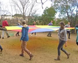 Un groupe d'adultes tournent en tenant une toile de parachute colorée