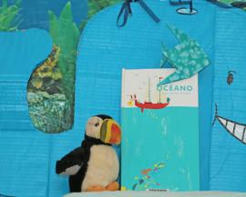 Un livre est posé devant une baleine en carton et à côté d'un macareux en peluche