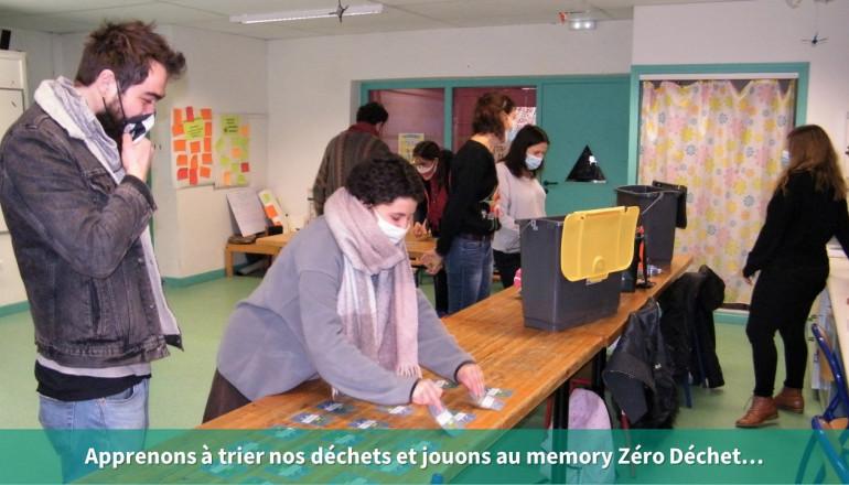 Dans une salle, des participants classent les déchets dans différentes poubelles et au premier plan, des agents, jouent à un jeu de cartes