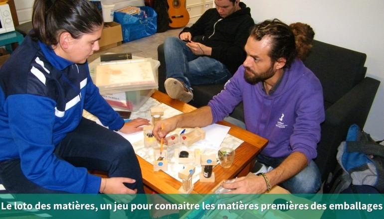 Un agent de l'Écolothèque montre un jeu sur les matières premières à un agent communal