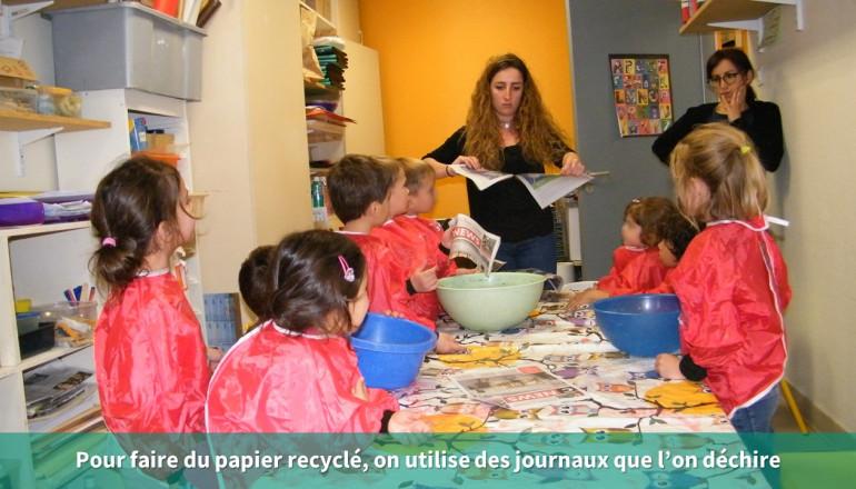 Une animatrice déchire des feuilles de papier journal pour faire du papier recyclé