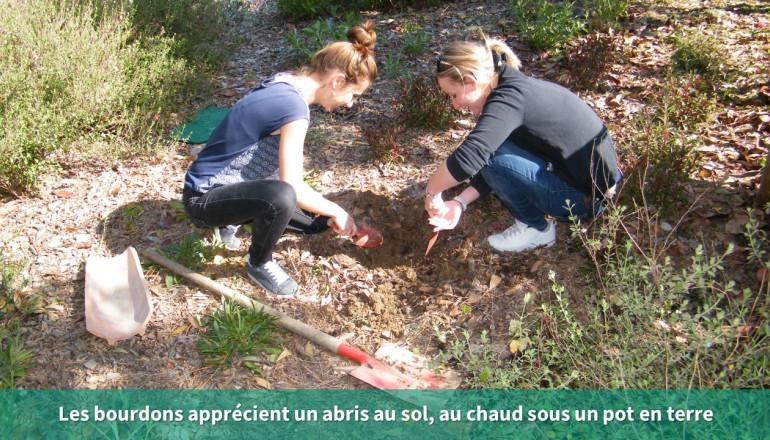 Deux personnes creusent un trou dans le sol pour installer un pot en terre qui servira d'abris aux bourdons