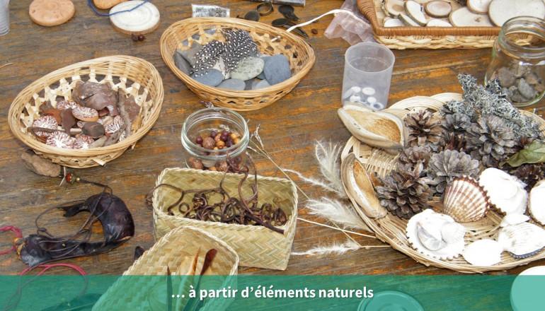 Gros plan sur une table sur laquelle différents éléments naturels sont disposés : coquillages, galets, plumes, pommes de pin...
