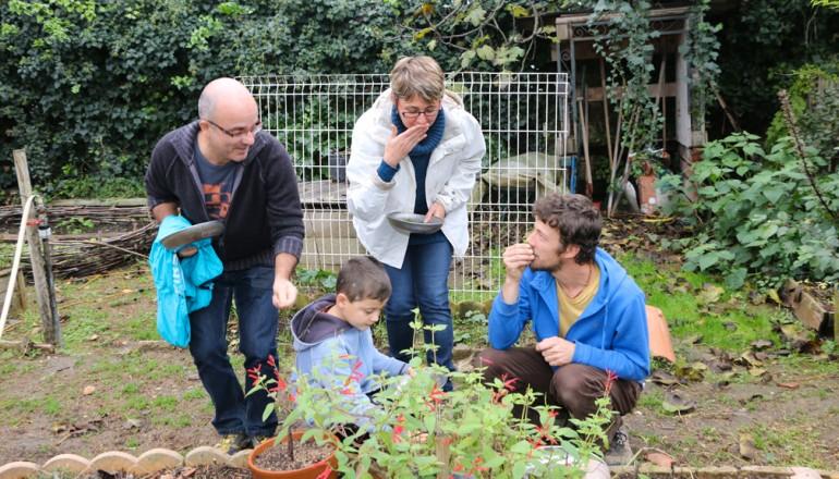 Un animateur de l'Écolothèque fait découvrir à des parents des herbes aromatiques.
