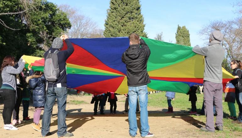 Des enfants inscrits à l'Accueil de loisirs de l'Écolothèque accompagnés de leurs parents jouent au jeu du parachute dans le grand pré
