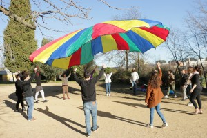 un groupe d'agents s'amuse avec le jeu du parachute coopératif