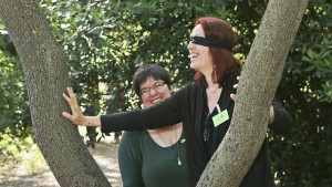 Une participante, les yeux bandés essaye de trouver son chemin avec une autre qui la guide