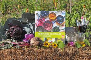 Livre mis en scène au potager avec des légumes et des fleurs dont on peut extraire la couleurs.
