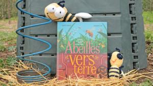 Un livre est posé devant un composteur avec deux abeilles en tricot posées dessus et à côté ainsi qu'un outil permettant d'aérer le compost