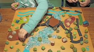 Des mains d'enfants manipulent des éléments de la malle Ricochets