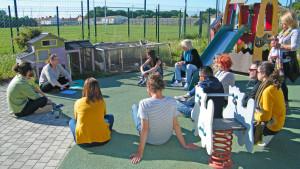 un groupe de 10 personnes sont assises dans la cour de récréation