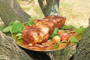Cake sur une assiette dorée posé dans un arbre avec des abricots et des amandes autour