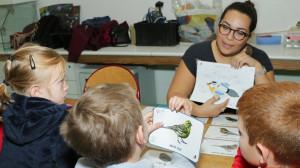 Une animatrice montre un schéma sur l'anatomie d'un oiseau à trois enfants dont un tient dans la main une image de serin cini