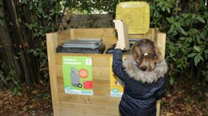 Un enfant est devant les poubelles grises et jaunes et trie du carton