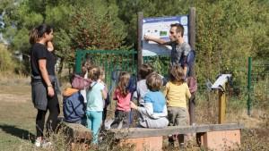 des enfants écoutent un enseignant leur expliquer l'écosystème de la mare