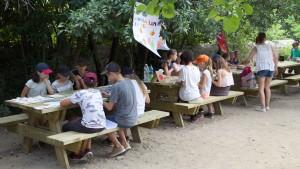 des enfants aurour de tables proposent leurs stands sur le thème de la lumière