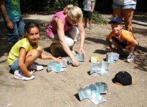 Des enfants accompagnés d'une animatrice utilisent des chauffe-verres solaire pour chauffer de l'eau