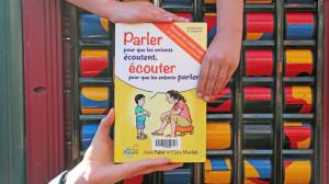 Un livre est tenu par le bas par une main d'adulte et par le haut par deux mains d'enfants