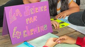 panneau posé sur une table avec écrit La science par 4 Chemins