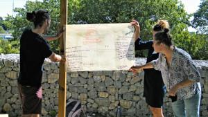 3 personnes tiennent une feuille sur laquelle les objectifs à atteindre sont inscrits