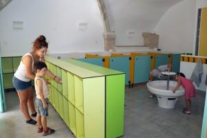 Un enfant accompagné d'un animateur récupère des affaires dans son casier pendant que deux autres boivent à la fontaine des nouveaux sanitaires du centre maternel