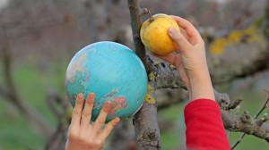 Deux mains d'enfants tiennent une pomme et un globe terrestre