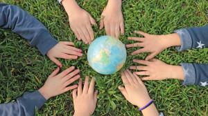 des mains d'enfants encerclent un planisphère