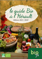 Couverture du guide Bio de l'Hérault - Édition 2021-2022 composée d'une photo de fruits et légumes, de fromages, d'un pot de miel, d'œufs, d'un pain, d'une bouteille de vin et d'une de jus de pomme